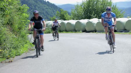 francja : VRHNIKA, SLOVENIA - JUNE 2014: Young bicyclist passing by an old woman on road. Driving in front of cyclists on empty road on a sunny day. Professional bicycling competition around countryside.