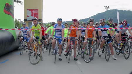 francja : VRHNIKA, SLOVENIA - JUNE 2014: Professional cyclists waiting on starting line. Wide shot of big group of bicyclists waiting for competition to begin.