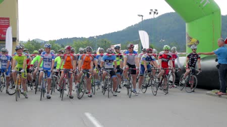 тур : VRHNIKA, SLOVENIA - JUNE 2014: Start of bicycle race. Cutting rope of start line and bicyclists begin the bicycle race through town. Стоковые видеозаписи