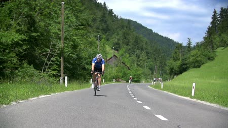vyhlídkové : VRHNIKA, SLOVENIA - JUNE 2014: SLOW MOV: Biking in nature. Wide shot of bicyclist in nature driving down the road in professional outfit and bike.