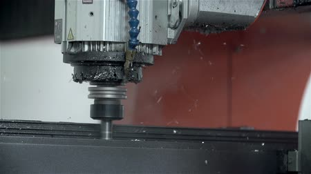 mecânica : Drilling holes in slow motion. Computer guided machine drills hole into metal very precisely filmed in slow motion