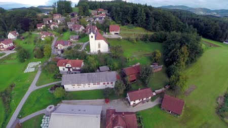 vista frontal : CELJE, SLOVENIA - SEPTEMBER 2014: Small village with the church in a countryside in nature. Aerial fly over shoot of small village with the church in a countryside in nature Stock Footage