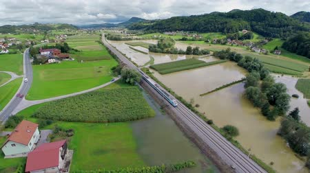 elpusztított : Flying over train stopping beside flooded countryside fields. Aerial landscape shot of flooded farm lands while passenger train travel through stopping because of possible danger.