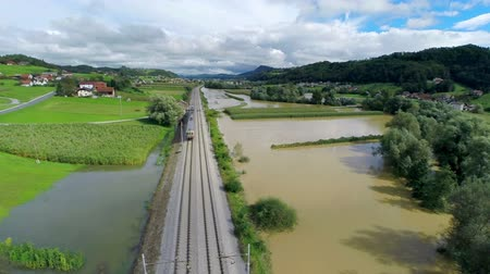 destruído : Flying over train tracks with train in flooded valley. Flying over train tracks with train slowly progressing over flooded valley.
