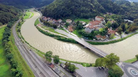 pojistka : Flying over river making curve through town to valley. Wide aerial shot of river running through Celje city making a turn in to valley. Dostupné videozáznamy