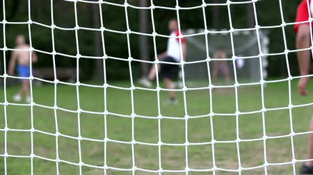 göller : Behind the goal focus on net . Slow motion footage of a children who are playing the game of football and the cameras focus is on the goal net. Stok Video