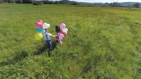 Lovely young couple kids running with balloons. Aerial slow motion shoot of two lovely couple kids, boy and girl and running of the camera on a big green grass field in the middle of nowhere