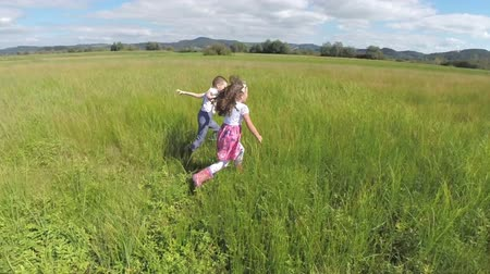 outside : Two kids enjoy life and looking to the camera while running. Two children happily running on a grass field feeling free and looking to the camera