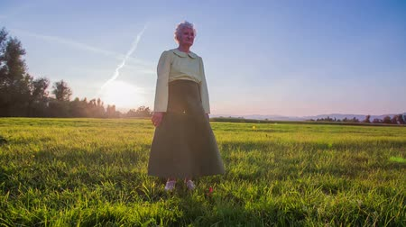 walk behind : old grandma standing in front of the camera at sunset. Slow motion RAW footage of old grandma standing in front of the camera in green suit an a grass field at sunset and ray come behind her