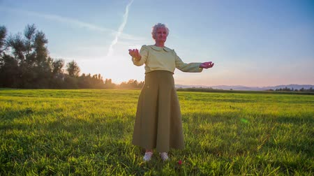 régi : Granny standing in the middle of green lawn. Wide jib shot of old woman in green long skirt with sunset in background standing on big green field.
