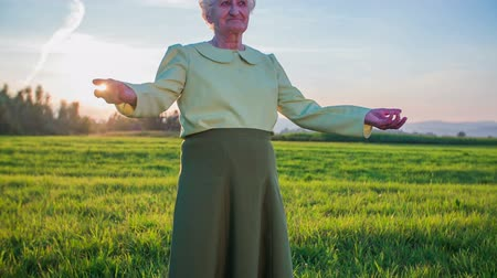 tek başına : Old woman raising arms in an idyllic scene. Jib shot of old granny in long green skirt standing on lawn with sunset in background raise her hands in slow motion.
