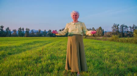 régi : Granny raising hands on lawn wide shot. Old woman with grey hair and long skirt raising hands standing on green lawn.