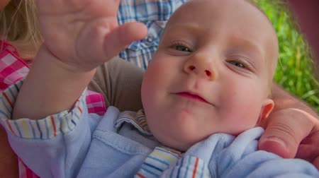 just born : Just born small child try to catch the camera. Slow motion RAW shoot of a young child in a mothers hands smile to the camera and try to grab it while they are sitting under a tree near a green grass field in a summer sunny day. Stock Footage
