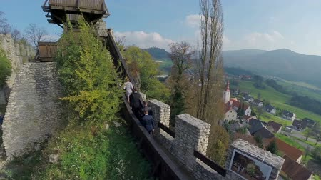 к северу : Beautiful view of the medieval castle. On these footage four business partners walking towards the lookout spot in the middle of the castle with beautiful background.