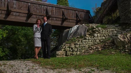 lengyelország : Business couple standing in the middle of the ruins. Slow motion footage of the business couple standing in the middle of the castle ruins in the beautiful land scape on sunny day.