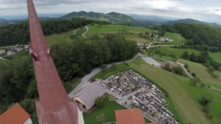 bakış : SENTJUR, SLOVENIA - SEPTEMBER 2014: Flying over church on top of a hill. on this footage camera fly over church on to of the hill and keep on filming the wonderful landscape on nice summer day.