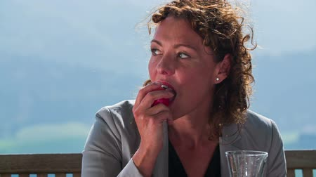 ebéd : Business lady choose healthy lifestyle. Slow motion close-up footage of a beautiful business woman picking up the apple in the middle of the nice landscape on sunny summer day.