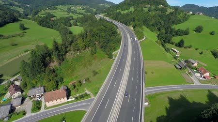 otoyol : Highway bridge crossing motorway under the bridge. Aerial shoot of a highway bridge in a nature crossing motorway road under the bridge Stok Video