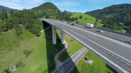 mosty : Motorway under the bridge and highway road. Aerial lifting up close up shot of a motorway road with traffic under the bridge and highway road with cars and truck on the bridge