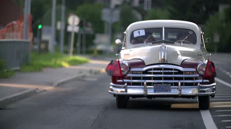 elliler : LUKOVICA, SLOVENIA - AUGUST 2014: Row of cool oldtimers. Close-up slow motion shoot of an american beauty cruising down the country rode on sunny summer day.