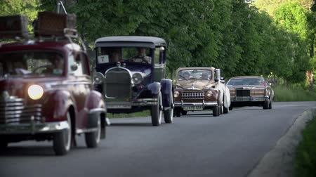 sběratelskou : LUKOVICA, SLOVENIA - AUGUST 2014: Line of vinatge cars in slow motion. Slow motion shot of amazing and rare old-timers while driving on the road