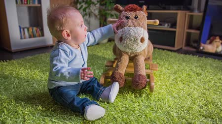 just born : Just born child caress plush horse.. On this close-up slow motion footages of a cute joust born child sitting on the green carpet and stretched out his hands towards the plush toy.