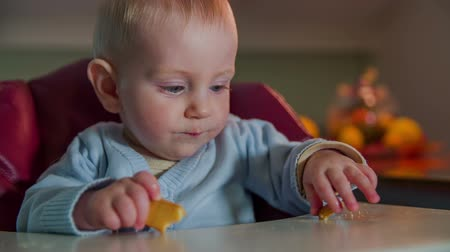 just born : Just born child picking up the piece biscuit. Close-up slow motion footage of a just born child picking up the piece of biscuit from a table in the nice flat.