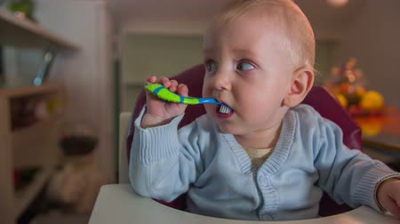 just born : Little child brushing his teeth. On this slow motion close up footage is a just born child sitting in the red chair and brushing his teeth in the nice flat.
