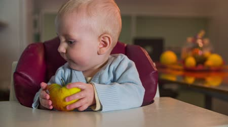just born : Just born child with half an apple in his hands . Close-up slow motion footage of a small blue eyes just born child with the half apple in his hands and he sits in the red chair.