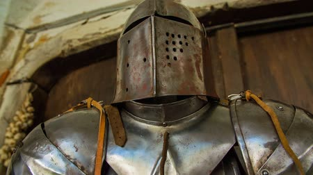 zbroja : Metal armour helmet on the stand . On this close-up RAW footage is armour who stand on the wooden stand in front of wooden doors on sunny day.