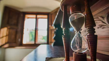 kum saati : Time is running in the hourglass. Close up slow motion footage of a hourglass standing on the vintage wooden table and time is running. Stok Video