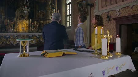 church utensils : The study of religious paintings. Zooming-in footage of a priest showing the middle age couple the artwork in these beautiful catholic church. Stock Footage