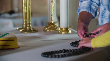 church utensils : Beginning with the rosary prayer. Close-up slow motion raw footages of a couple picking up the rosary to start the praying in the middle of the church.