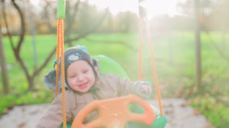 houpavý : Nice day for playing on home swing. Slow motion close-up shoot of a small smiling baby boy swinging on a backyard swing on a cold sunny day.