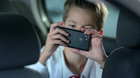 śmiech : Child playing with a phone on the back seat. Close up footage of a small boy playing with phone on the while seating in the back seat in the car. Wideo