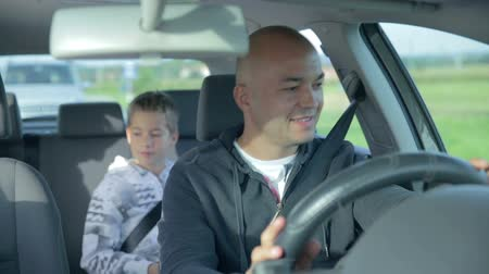 apa : Father and son enjoy the drive and then something hits the windshield. On this footage the happy father an the son in the back seat enjoying the drive and then something hits the front window of the car.