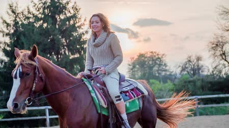 koňmo : Woman on the horse with a sunset in the background. Slow motion RAW footage of a beautiful woman ridding the horse on a ranch with beautiful sunset in the background.
