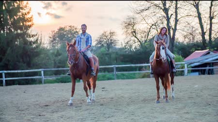 koňmo : Couple sitting on the horse. Slow motion RAW footage of a couple sitting on the horses in the middle of the ranch on a countryside. Dostupné videozáznamy