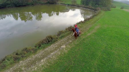koňmo : Horseback riding in the beautiful scenery  . Slow motion helicopter RAW footage of a couple of people riding a horses in the beautiful scenery near the lake. Dostupné videozáznamy