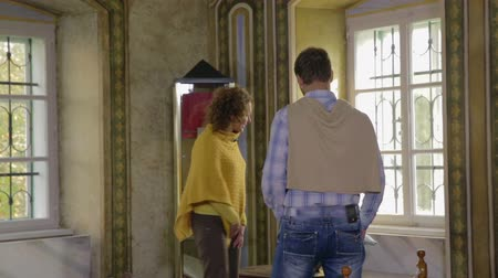 galeria : Beautiful couple walking across the room full of historic art   . Close-up footage of a couple walking across the room in the house museum of a historic writer and the priest from medieval times. Stock Footage