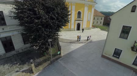 toscana : Big church in the middle of the village . Helicopter camera zooming out footage of a couple walking on the square in front of the church on the sunny day on the village.
