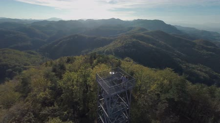 schody : Lookout tower rising in the middle of the forest. Zooming out helicopter camera flaying above the couple standing on the tower in the middle of the forest with beautiful view. Wideo