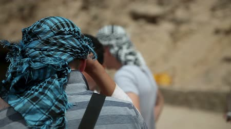 camelo : EGYPT, SAFARI - JUL, 2013: Detail shot of tourist guide covering the tourists with palestinian scarfs