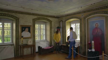výstava : SENTJUR, SLOVENIA - OCTOBER 2014: Couple walks in the room of the historic person. On this footage we can see the couple walking around the museum room of a important historic catholic person.