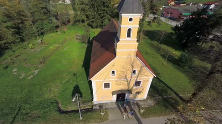 pacífico : People goes in to the small catholic church . Helicopter camera flaying above the church in witch are going the grope of people in the middle of a countryside on the sunny day. Stock Footage