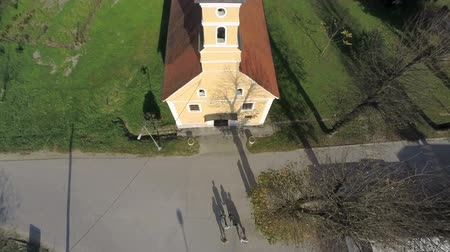 pacífico : The grope of tourists are going in the local church . Helicopter camera flaying above the grope of people going in to the catholic church in the middle of a countryside on the sunny day.