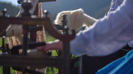 wełna : Working on a wooden tool for processing the cotten. Close up RAW footage of a elderly woman seating outdoors and processing the wool on a sunny day.