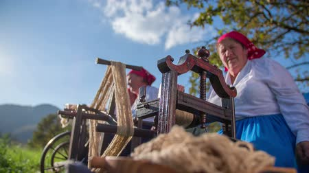 wełna : Processing the wool with wooden tool. Slow motion RAW footage of a woman on the beautiful day processing wool on the wooden tool in the countryside.