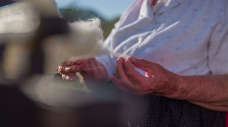 wełna : Elderly woman making a string from wool. Slow motion close up RAW footage of a elderly woman seating on the bench and making a string from wool on a sunny day.