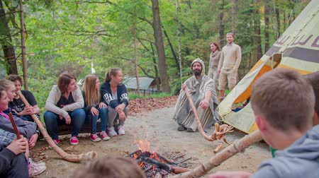 sátor : Join to the children around the camp fire. Slow motion RAW footage of a couple comes to the camp fire surrender by the children playing the didgeridoo on the sunny day. Stock mozgókép
